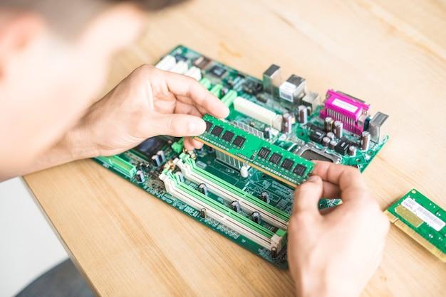 Mężczyzna it technik trzyma moduł pamięci ram w płycie głównej