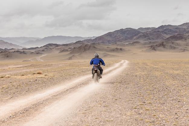Mężczyzna jadący na motocyklu po stepach mongolii, na wzgórzach mongolii