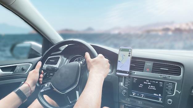 Mężczyzna jadący samochodem przejeżdżający obok pięknego leśnego krajobrazu. wynajem samochodów, koncepcja jazdy samochodem, format banera.