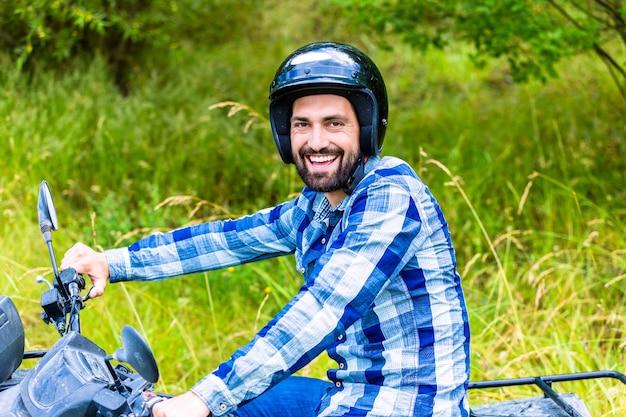 Mężczyzna jadący w terenie z quadem lub quadem