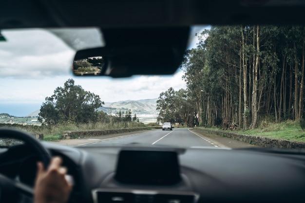 Mężczyzna jazdy samochodem z widokiem od wewnątrz.