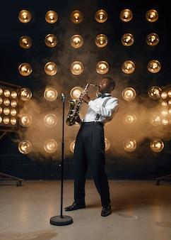 Mężczyzna jazzman gra na saksofonie na scenie z reflektorami. czarny muzyk jazzowy występujący na scenie