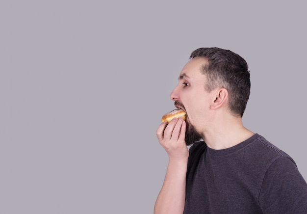 Mężczyzna je babeczkę nad szarym tłem z brodą