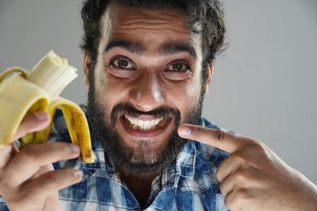 Mężczyzna je banana i pokazuje zęby