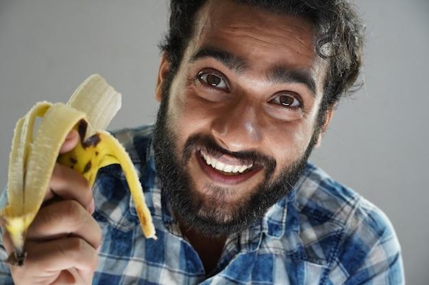 Mężczyzna je banana i szczęśliwy