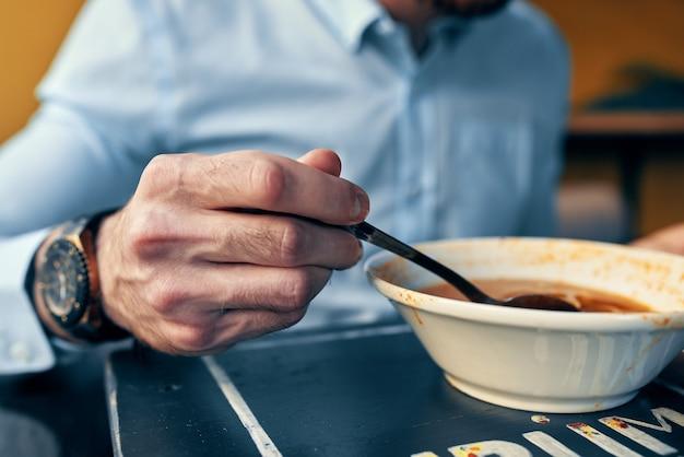 Mężczyzna je barszcz ze śmietaną w restauracji przy stoliku w kawiarni z zegarkiem w ręku