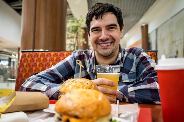 Mężczyzna je burger fast food i sam pije piwo na otwartej przestrzeni restauracji w centrum handlowym.