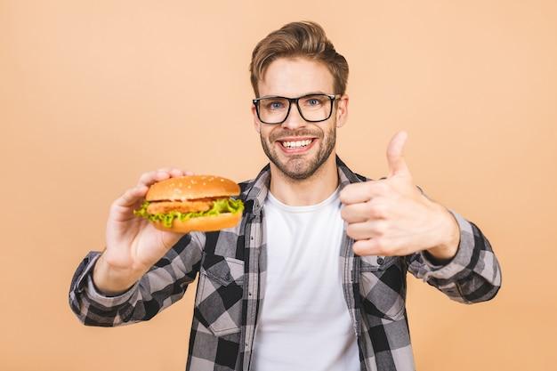 Mężczyzna je burgera w studio