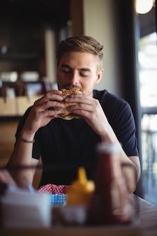 Mężczyzna je burgera