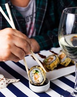 Mężczyzna je gorące rolki sushi z sosem sojowym