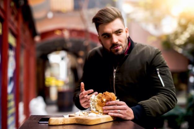 Mężczyzna je hamburger przy ulicą. pyszny burger.