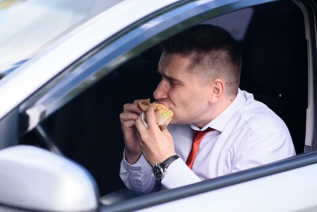 Mężczyzna je hamburgera w samochodzie.
