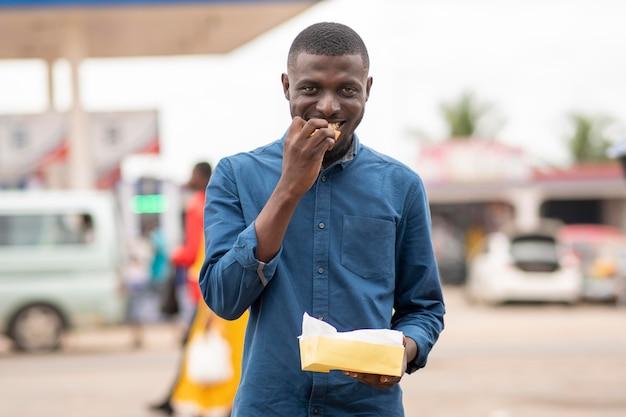 Mężczyzna je jedzenie uliczne?