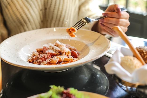 Mężczyzna je makaron penne z sosem pomidorowym, parmezanem, warzywami, mięsem, widok z boku