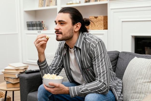 Mężczyzna je popcorn i ogląda telewizję na kanapie
