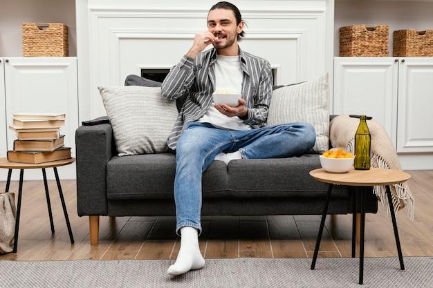 Mężczyzna je popcorn i ogląda telewizję z daleka