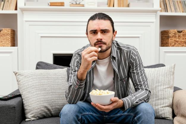 Mężczyzna je popcorn i ogląda telewizję
