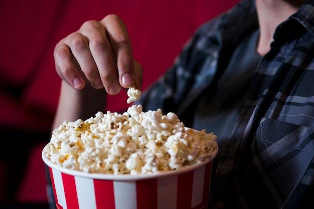 Mężczyzna je popcorn w kinie