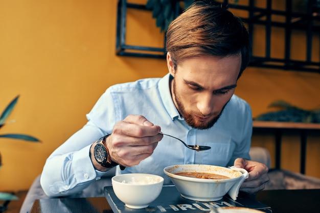Mężczyzna je przekąskę zupy na lunch w restauracji?