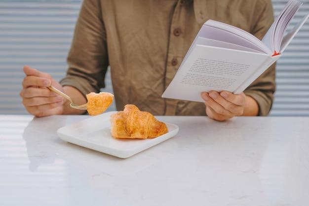 Mężczyzna je śniadanie i czyta książkę siedząc przy białym stole