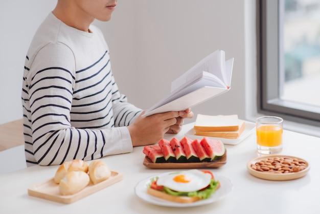 Mężczyzna je śniadanie i czyta książkę w domu w godzinach porannych.