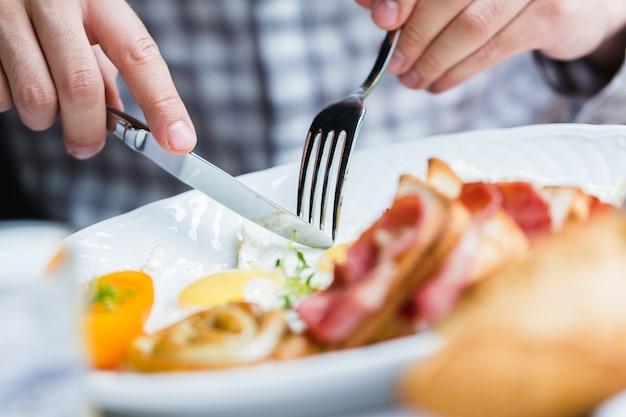 Mężczyzna je śniadanie widelcem i nożem, z bliska