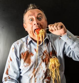 Mężczyzna je spaghetti z sosem pomidorowym