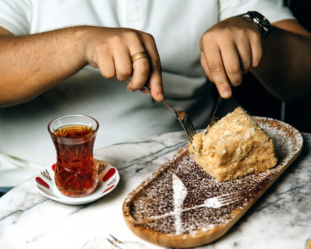 Mężczyzna je tort z herbatą