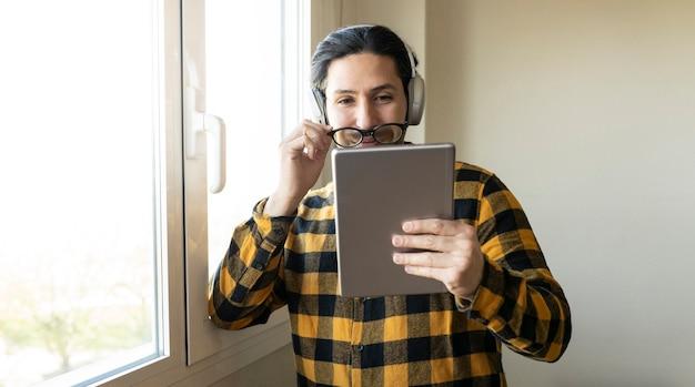 Mężczyzna jedną ręką zdejmuje okulary, a drugą trzyma tablet przy oknie