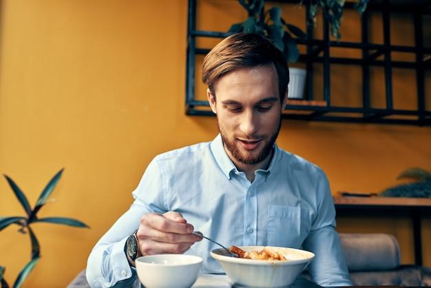 Mężczyzna jedzący lunch przy stoliku kawiarnianym w pracy i we wnętrzu