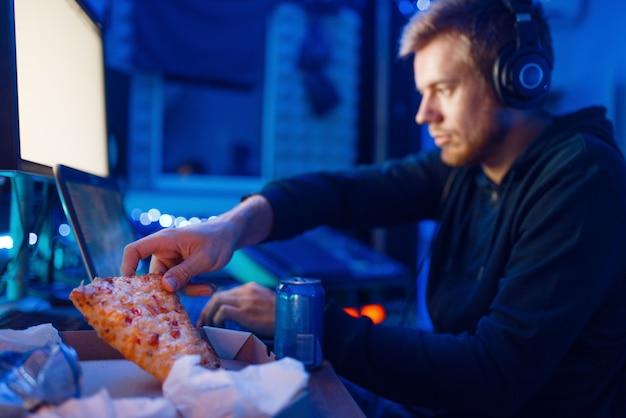 Mężczyzna jedzący pizzę w miejscu pracy z laptopem i komputerem stacjonarnym, gamingowy styl życia, nocny turniej. gracz gier komputerowych w swoim pokoju z neonowym światłem, streamer