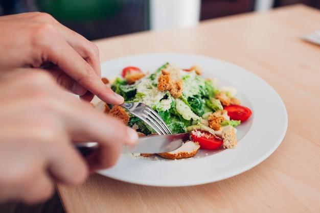 Mężczyzna jedzenie sałatki cezara w restauracji. o smaczne, zdrowe jedzenie w kawiarni.