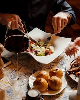 Mężczyzna jedzenie sałatki wołowej z sałatą i pomidorem w restauracji
