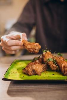 Mężczyzna jedzenie smażonego kurczaka z sosem w kawiarni