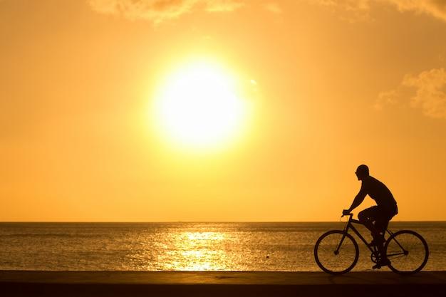 Mężczyzna jedzie bicykle outdoors przeciw zmierzchowi. sylwetka.