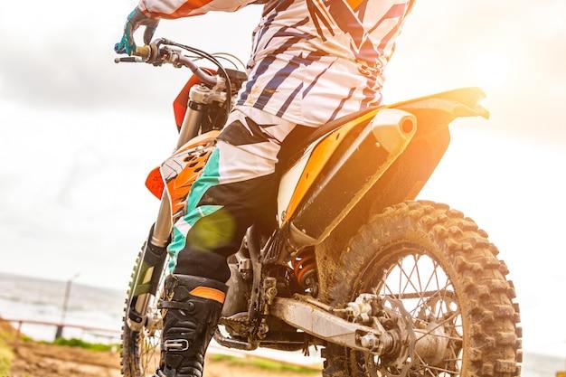 Mężczyzna jedzie motocross w ochronnym kostiumu w błocie