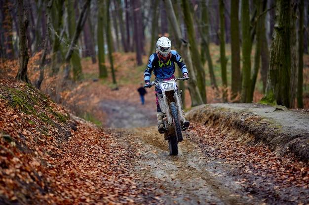 Mężczyzna jedzie motocykl szybko w jesień lesie.