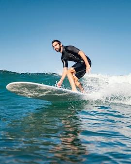 Mężczyzna jedzie na desce surfingowej i dobrze się bawi