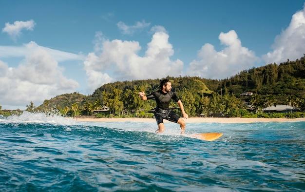 Mężczyzna jedzie na desce surfingowej i miło spędza czas ujęcie poziome