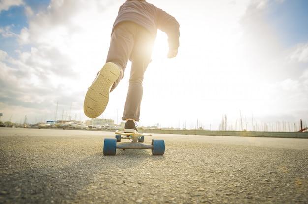 Mężczyzna jedzie na deskorolce na drodze - ludzie rasy kaukaskiej - ludzie, sport i koncepcja skateboardingu