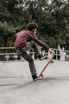 Mężczyzna jedzie na deskorolce na świeżym powietrzu w parku