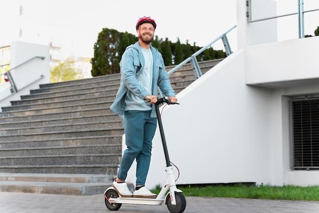 Mężczyzna jedzie na eko skuterze po mieście