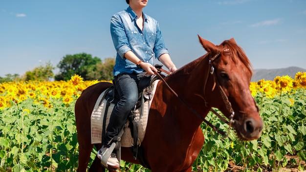 Mężczyzna jedzie na koniu w polu słoneczników na niebieskim tle nieba - wolność i szczęście.