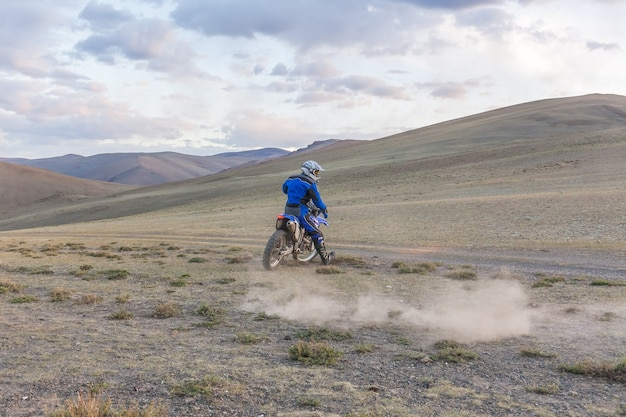 Mężczyzna jedzie na motocyklu crossowym po stepach mongolii, na wzgórzach mongolii