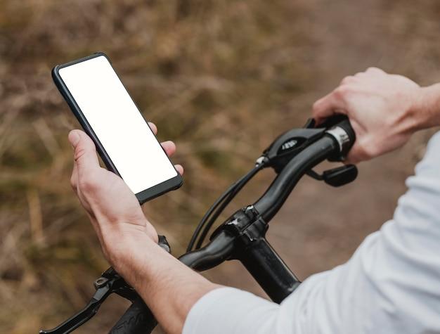Mężczyzna jedzie na rowerze górskim i sprawdza swój telefon
