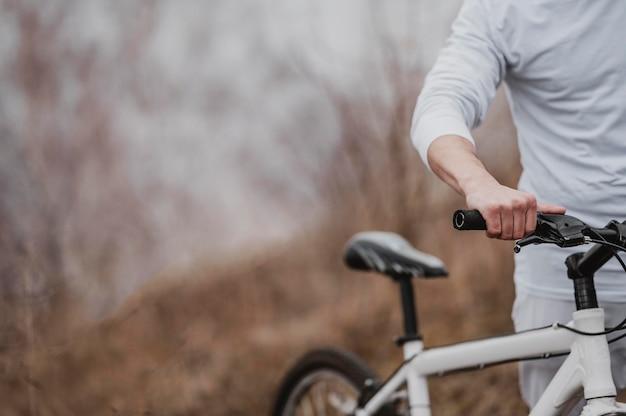Mężczyzna jedzie na rowerze górskim w specjalnym sprzęcie z miejscem na kopię