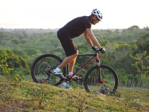Mężczyzna jedzie na rowerze po górach. piękny letni dzień. rowerzysta na szczycie wzgórza.