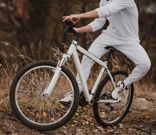 Mężczyzna jedzie na rowerze w białych ubraniach