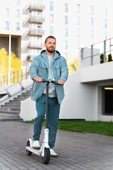 Mężczyzna jedzie na skuterze na zewnątrz