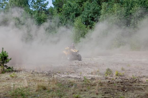 Mężczyzna jedzie na żółtym quadzie atv pojazd terenowy po piaszczystym lesie. sport ekstremalny ruch, przygoda, atrakcja turystyczna.
